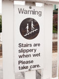 Una señal de peligro que dice las escaleras es resbaladiza cuando es mojada toma por favor c Imagen de archivo libre de regalías