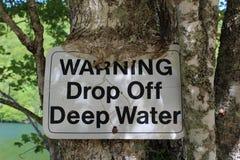 Una señal de peligro que es absorbida por un árbol en las orillas de la ley del ` del lago O sobre la Isla de Cabo Bretón Fotos de archivo