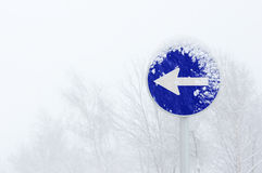 Una señal de tráfico obligatoria de la dirección de la manera con la ventisca Imagenes de archivo