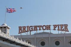 Una señalización de Brighton Pier con la bandera inglesa Imágenes de archivo libres de regalías