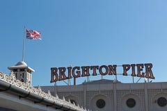 Una señalización de Brighton Pier con la bandera inglesa Fotografía de archivo