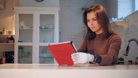 Una señora con un brazo robótico está actuando una tableta