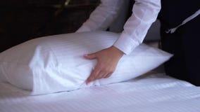 Una señora de la limpieza del hotel endereza una almohada en una habitación pequeña, acogedora metrajes