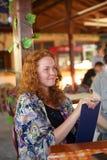 Una señora elegante envuelta en una bufanda colorida en negociaciones Imagenes de archivo