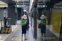Una señora espera la línea 6 del subterráneo Foto de archivo libre de regalías