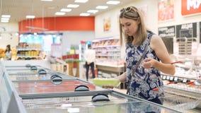 Una señora femenina coge productos del refrigerador almacen de video