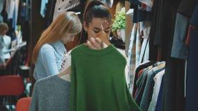 Una señora hermosa en una tienda de ropa elige un guardarropa conveniente para sí misma almacen de metraje de vídeo
