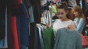 Una señora hermosa en una tienda de ropa elige un guardarropa conveniente para sí misma metrajes