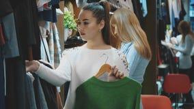 Una señora hermosa en una tienda de ropa elige un guardarropa conveniente para sí misma almacen de video