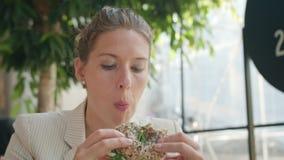 Una señora joven Eating Sandwich en el café almacen de metraje de vídeo
