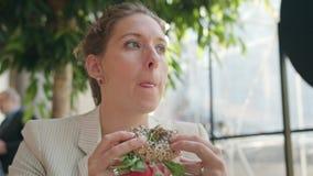 Una señora joven Eating Sandwich en el café almacen de video