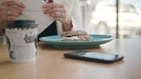 Una señora joven Eating Sandwich en el café metrajes