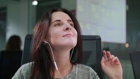 Una señora joven Listening a la música dentro almacen de video
