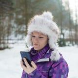 Una señora joven que mira en el teléfono móvil Foto de archivo libre de regalías