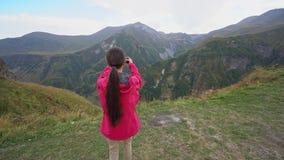 Una señora joven Taking Photos en las montañas almacen de metraje de vídeo