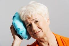 Una señora mayor con el bolso de hielo por su cabeza. Imagen de archivo