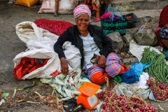 Una señora mayor en un sombrero interesante vende verduras en el mercado callejero auténtico y colorido indonesio local fotografía de archivo