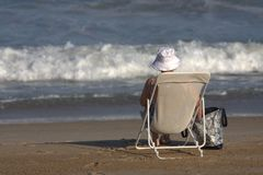 Una señora mayor que se sienta en una silla en la playa Imágenes de archivo libres de regalías