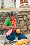 Una señora mayor que vende los mangos en la calle Imágenes de archivo libres de regalías
