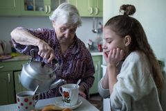 Una señora mayor trata un desayuno de la niña, sentándose en la tabla en su casa foto de archivo libre de regalías