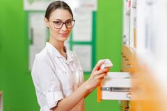 Una señora oscuro-cabelluda delgada sonriente con los vidrios, llevando un guardapolvo médico, sostiene un paquete de píldoras y  fotografía de archivo