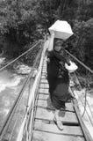 Una señora que camina en puente de madera sobre un río grande Foto de archivo libre de regalías