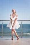 Una señora que presenta en una terraza del ` s del hotel La hembra sonriente en un fondo brillante del cielo La muchacha elegante Fotografía de archivo libre de regalías