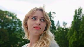 Una señora rubia joven Turning Back su cabeza al aire libre almacen de video