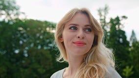 Una señora rubia joven Turning Back su cabeza al aire libre almacen de metraje de vídeo