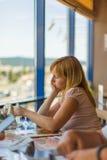 Una señora rubia pensativa está observando una tarjeta de la promoción Imágenes de archivo libres de regalías