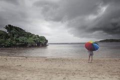 Una señora y un paraguas colorido foto de archivo
