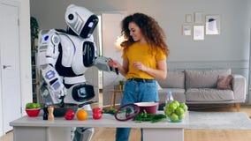 Una señora y un robot son de cocinar y que intentan la comida almacen de video