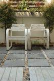Una sedia di due braccioli in poco giardino Immagini Stock