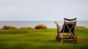 Una sedia di legno vicino ad una spiaggia di sabbia bianca che guarda all'oceano fotografia stock
