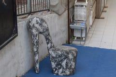 Una sedia a forma di dei tacchi alti alla via urbana fotografie stock