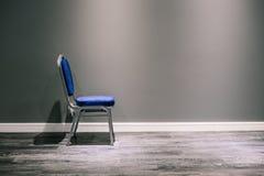 Una sedia sola con le gambe d'argento in blu Sta alla parete grigia Al fondo di ampi battiscopa e laminato bianchi E fotografie stock