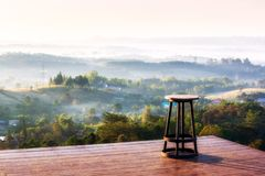 Una sedia sulla cima della collina quindi che si siede e considerare della catena montuosa di Khao-Kho più con nebbia nuvolosa, i immagini stock