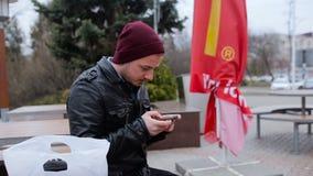 Una seduta del giovane esterna ed esaminare il suo telefono archivi video