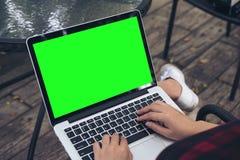 Una seduta della donna, usando e scrivendo sul computer portatile con lo schermo verde in bianco sulla coscia al fondo all'aperto immagine stock