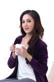 Una seduta e una holding della donna una tazza Immagine Stock Libera da Diritti