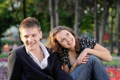 Una seduta sorridente delle coppie Fotografie Stock