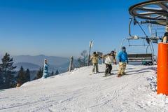 Una seggiovia seguente di tre snowboarders Immagini Stock