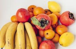Una selección de diversas frutas frescas dispuestas de plátanos, de mandarines, de caquis y de limones en el cierre blanco del fo fotografía de archivo