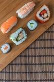 Una selezione dei rotoli di sushi del pesce fresco sul bordo di bambù Fotografie Stock Libere da Diritti