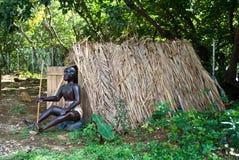 Una sentada auxiliar delante de una casa de la paja Imagen de archivo libre de regalías