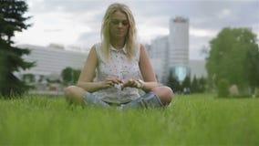 Una sentada de la muchacha entrecruzada en un césped metrajes