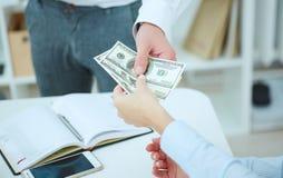 Una serie d'offerta dell'uomo di cento banconote in dollari Immagine Stock