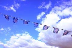 Una serie di bandiere di plastica sbiadite del sindacato che volano contro un cielo blu nuvoloso Fotografie Stock