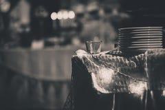 Una serie di piatti bianchi sulla tavola con illuminazione della stella ed il fondo della sfuocatura Fotografie Stock