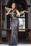 Una serpiente morena hispánica hermosa del constrictor de boa de Poses With A del modelo alrededor de su cuerpo fotografía de archivo